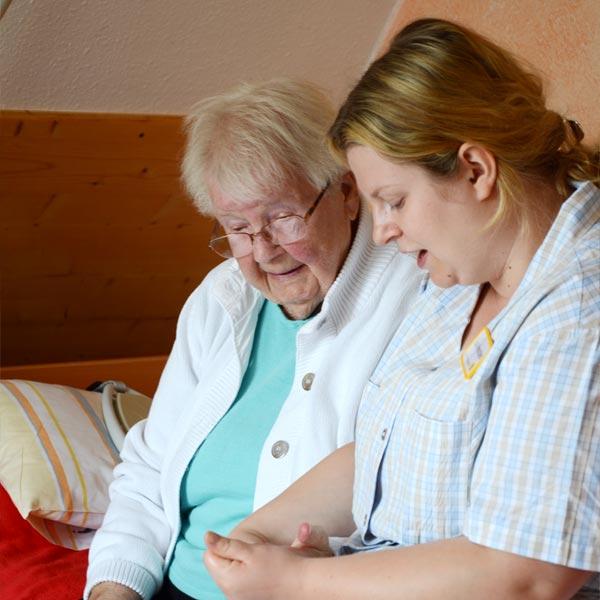 Seniorin mit Pflegerin bei Blutzuckerkontrolle